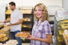 Portrait d'une femme blonde de sourire prenant une pâtisserie Photographie stock libre de droits