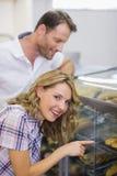 Portrait d'une femme blonde de sourire regardant la pâtisserie Photos libres de droits