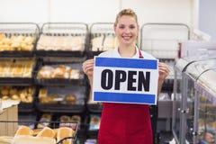 Portrait d'une femme blonde de sourire tenant un signe Photographie stock libre de droits