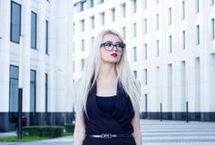 Portrait d'une femme blonde intelligente sur le fond du centre d'affaires Images libres de droits