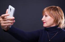 Portrait d'une femme d'une cinquantaine d'années faisant la photo de selfie avec le smartphone sur un fond noir Photos stock