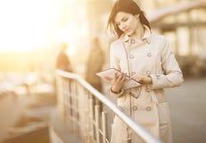 Portrait d'une femme d'affaires avec le comprimé et les personnes à l'arrière-plan le jour ensoleillé lumineux Image libre de droits