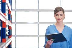 Portrait d'une femme d'affaires avec le presse-papiers dans l'entrepôt Photo stock