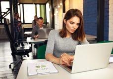 Portrait d'une femme d'affaires sérieuse à l'aide de l'ordinateur portable dans le bureau Photos libres de droits
