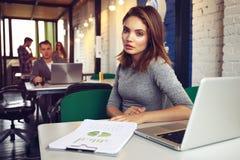 Portrait d'une femme d'affaires sérieuse à l'aide de l'ordinateur portable dans le bureau Photographie stock