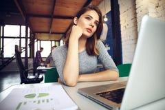 Portrait d'une femme d'affaires sérieuse à l'aide de l'ordinateur portable dans le bureau Image stock