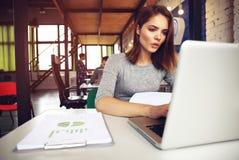 Portrait d'une femme d'affaires sérieuse à l'aide de l'ordinateur portable dans le bureau Photographie stock libre de droits