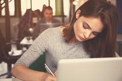 Portrait d'une femme d'affaires sérieuse à l'aide de l'ordinateur portable dans le bureau Photos stock