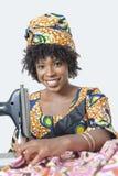 Portrait d'une femme d'Afro-américain à l'aide de la machine à coudre au-dessus du fond gris photographie stock