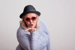 Portrait d'une femme de poids excessif attirante soufflant un baiser dans un studio image libre de droits
