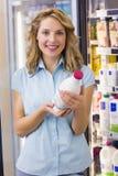 Portrait d'une femme de sourire ayant sur ses mains une bouteille à lait Photographie stock