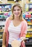 Portrait d'une femme de sourire payant à la caisse enregistreuse payant avec la carte de crédit Images stock