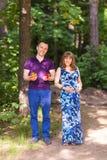 Portrait d'une femme enceinte caucasienne et de son mari tenant des jouets pour le bébé dehors Photos libres de droits