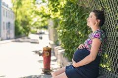Portrait d'une femme enceinte heureuse et fière sur le fond urbain images libres de droits