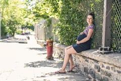 Portrait d'une femme enceinte heureuse et fière sur le fond urbain images stock