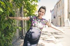 Portrait d'une femme enceinte heureuse et fière sur le fond urbain image libre de droits