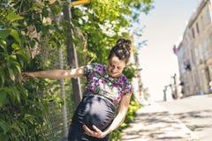 Portrait d'une femme enceinte heureuse et fière sur le fond urbain photographie stock