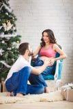 Portrait d'une femme enceinte heureuse tenant des chaussures de bébé et de elle Photo libre de droits