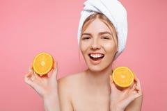 Portrait d'une femme gaie attirante avec une serviette enroulée autour de sa tête, tenant les tranches oranges au-dessus du fond  photographie stock libre de droits