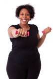 Portrait d'une femme grasse noire établissant avec les poids gratuits - Image libre de droits
