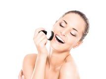 Portrait d'une femme heureuse tenant une brosse de maquillage Image stock