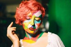 Portrait d'une femme intelligente avec les cheveux oranges et le maquillage multicolore images stock