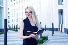 Portrait d'une femme intelligente regardant au carnet ouvert sur le fond du centre d'affaires Image stock