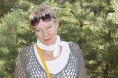Portrait d'une femme mûre avec des lunettes de soleil sur son front Images libres de droits