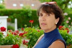 Portrait d'une femme mûre avec les verres rouges Image libre de droits