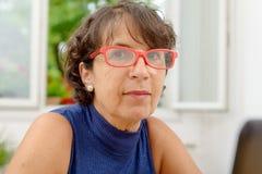 Portrait d'une femme mûre avec les verres rouges Photographie stock