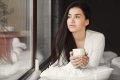 Portrait d'une femme par la fenêtre avec une tasse de café Photographie stock libre de droits