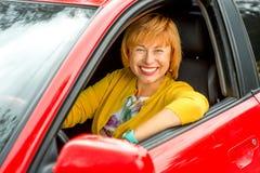 Portrait d'une femme plus âgée conduisant une voiture Image stock