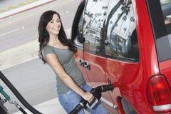Portrait d'une femme réapprovisionnant en combustible sa voiture Photos stock