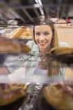 Portrait d'une femme regardant de nouveaux plats avec des pâtisseries Image stock