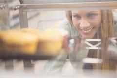 Portrait d'une femme regardant de nouveaux plats avec des pâtisseries Photographie stock