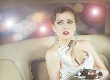 Portrait d'une femme riche mangeant du chocolat dans une voiture Photos libres de droits