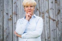 Portrait d'une femme supérieure active regardant l'appareil-photo avec stylos Photographie stock libre de droits