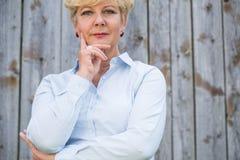 Portrait d'une femme supérieure active regardant l'appareil-photo avec stylos Image libre de droits