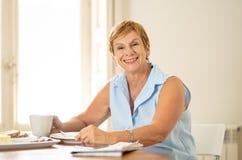 Portrait d'une femme supérieure heureuse ayant le café de matin photos stock