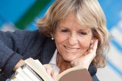 Femme supérieure lisant un livre Photos stock