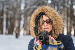 Portrait d'une femme tenant un appareil photo numérique dans les bois dans la victoire images libres de droits