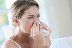 Portrait d'une femme éternuant et soufflant son nez Photographie stock libre de droits