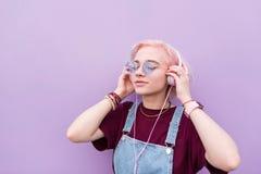 Portrait d'une fille élégante qui écoute la musique dans des écouteurs roses sur le fond d'un mur pourpre photos stock