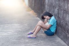 Portrait d'une fille asiatique triste et seule contre le dos grunge de mur Photographie stock