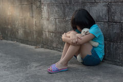 Portrait d'une fille asiatique triste et seule contre le dos grunge de mur Images libres de droits