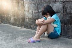Portrait d'une fille asiatique triste et seule contre le dos grunge de mur Photo stock