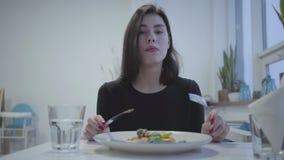 Portrait d'une fille assez jeune de brune mangeant dans un beau restaurant ou café banque de vidéos