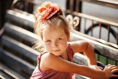 Portrait d'une fille assez petite s'asseyant sur un banc de parc Images libres de droits
