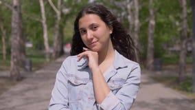 Portrait d'une fille attirante avec de longs cheveux La belle fille se tient sur la rue banque de vidéos