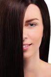 Portrait d'une fille aux cheveux foncés sur un fond blanc Photo stock